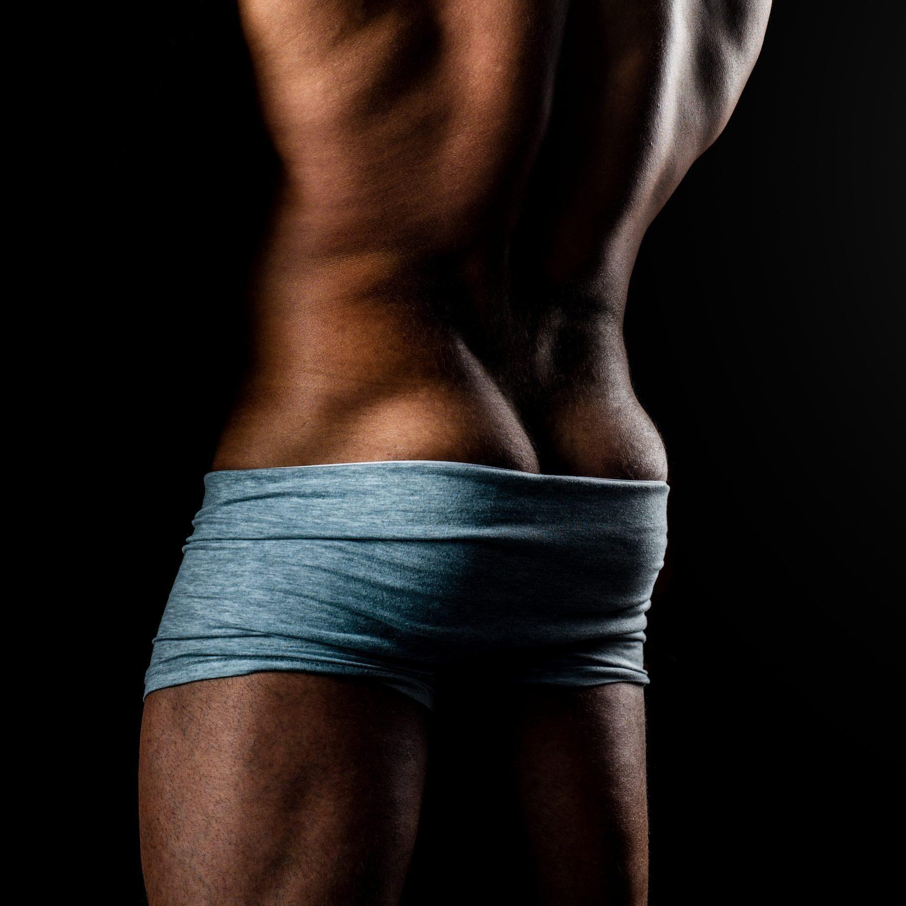 Muscular model man on dark background. Metrosexual concept. Nude torso. Topless male model. Man in underwear