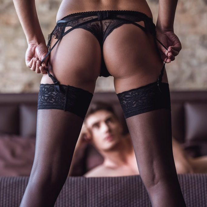 Back view of woman in black bikini and stockings, guy is lying on the bed
